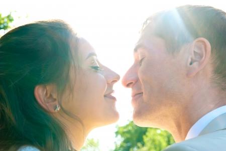 man woman kissing: bride and groom faces closeup