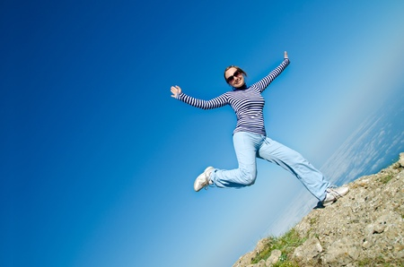 young woman jumping in mountain photo