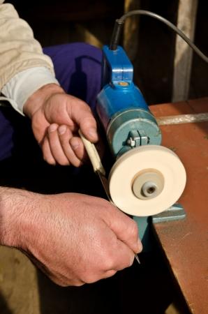 drudgery: a man sharpening old knife