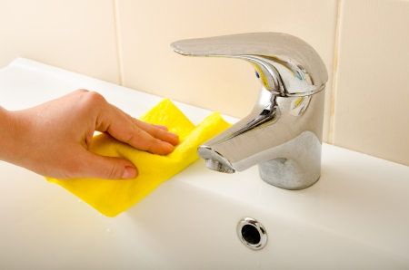 hand cleans tap with sponge photo