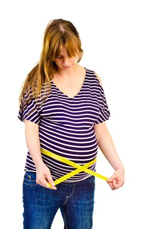 pregnant woman measuring her waist photo