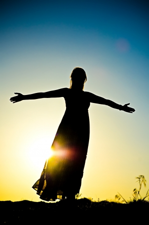 woman silhouette in front of a sunset Stock Photo - 21334689