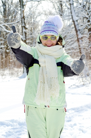 woman in winter giving a thumbs up photo
