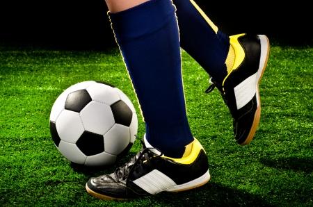 soccer player feet with ball closeup photo