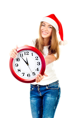young girl in christmas hat showing clock photo
