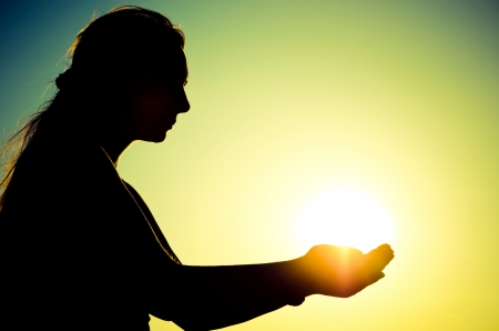 woman silhouette holding the sun photo