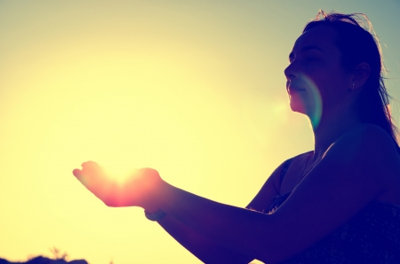 woman silhouette holding the sun Stock Photo