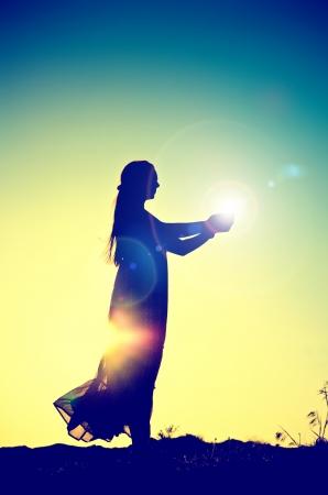woman silhouette holding the sun Standard-Bild