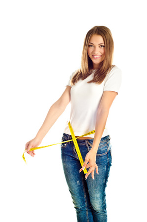 young girl measuring her waist isolated on a white background photo