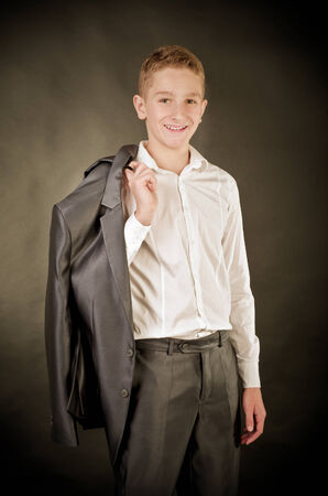 teenage boy in suit on a black background photo