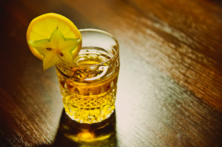 a cup of whiskey with lemon photo