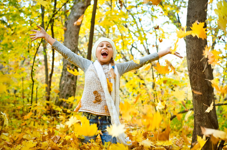 little girl throwing autumn leaves