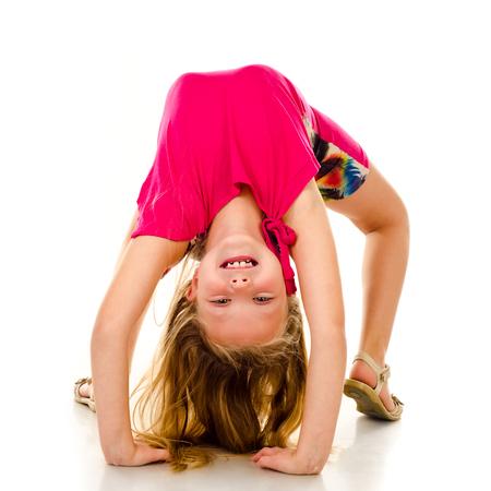 cabeza abajo: pequeña niña gimnasta aislado en un fondo blanco