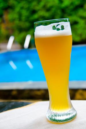 near beer: a goblet of beer near the pool outdoors