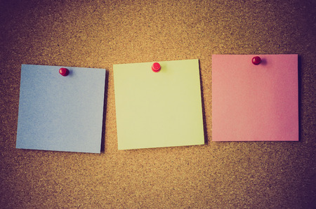 yellow tacks: blank note papers on a cork board