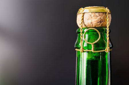 popping cork: green champagne bottle with cork closeup