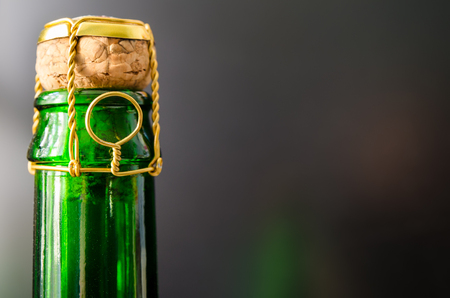 champagne pop: green champagne bottle with cork closeup
