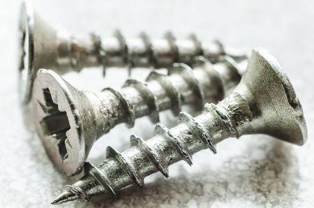 three metal screws macro closeup Stock Photo