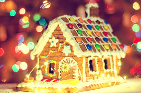 gingerbread house with blurred garland lights background