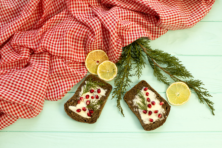 Black bread with grenades berries on turquoise wooden background. Christmas food, Christmas decorations with lemon, juniper, branch, red berries