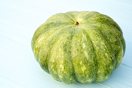 Green pumpkin on a turquoise wooden background