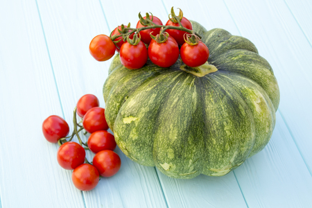 Green pumpkin and tomatoes on a turquoise wooden background