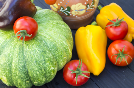 Green pumpkin, tomatoes, pepper and jug on a black wooden background Stock Photo