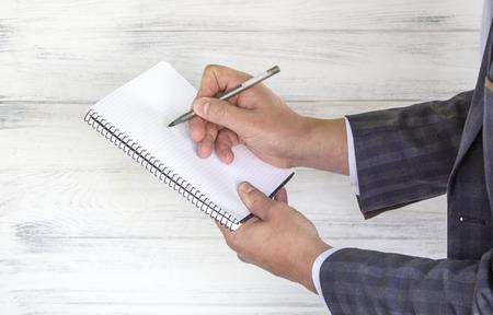 Businessman writing pen in notebook.