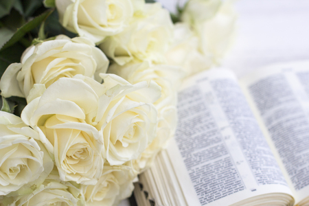 White roses and the Bible. White roses and the Bible on a white wooden background Фото со стока