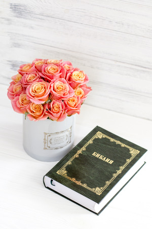 Roses in a round box and the Bible. Beautiful pink roses on a white wooden background. Beautiful pink roses and the Bible. Roses in a Hat Box