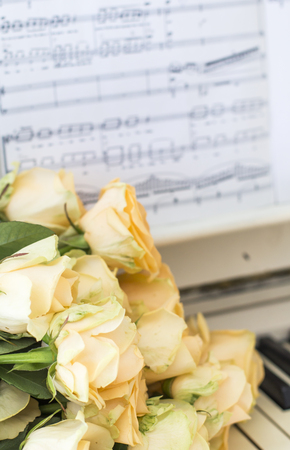 Peach roses on the piano with notes
