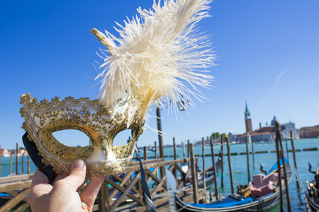 Venetian mask on the background of the gondolas in Venice