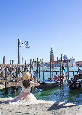 girl on berth with gondolas in Venice