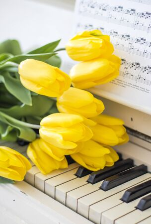 yellow tulips on a white piano with notes