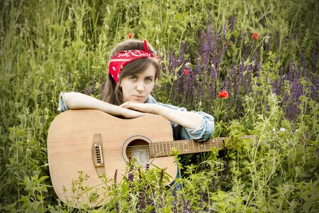 Beautiful girl with a guitar in poppies. Young woman on the grass. A teenager in a denim jacket and a red bandage. Retro style