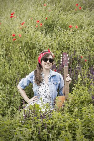 Beautiful girl with a guitar in poppies. Young woman in sunglasses on the grass. A teenager in a denim jacket and a red bandage. Retro style Stock Photo