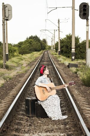 A beautiful girl plays the guitar. Pretty woman with old suitcases on the train tracksl. A teenager in a denim jacket, a long dress and a red bandage. Retro style