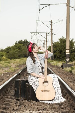 Beautiful girl with a guitar. Pretty woman with old  suitcases on the train tracks. A teenager in a denim jacket, a long dress and a red bandage. Retro style