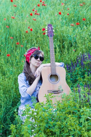 Beautiful girl with a guitar in poppies. Young woman in sunglasses on the grass. A teenager in a denim jacket and a red bandage.