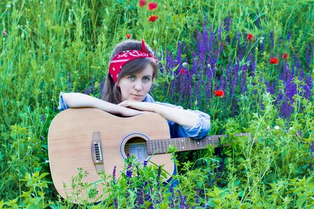 Beautiful girl with a guitar in poppies. Young woman on the grass. A teenager in a denim jacket and a red bandage.