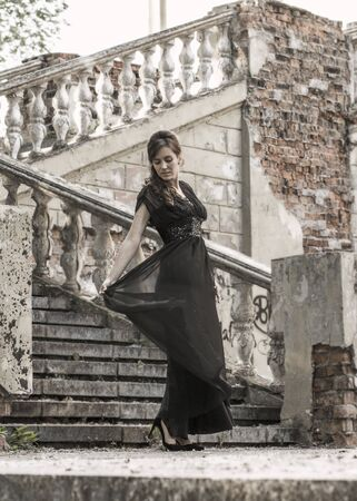 Beautiful girl in a black evening dress on the steps of an abandoned palace. Pretty woman with scars. Young girl in retro style. Pretty Woman