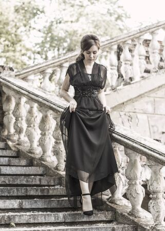 Beautiful girl in a black evening dress on the steps of an abandoned palace. Pretty woman with scars. Young girl in retro style. girl steps up the stairs. Pretty Woman 스톡 콘텐츠