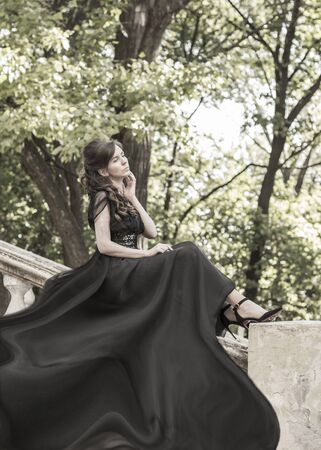 Beautiful girl in a black evening dress sits on the stair railing of an abandoned palace. Beautiful woman with scars. Retro style young girl. Pretty Woman 스톡 콘텐츠