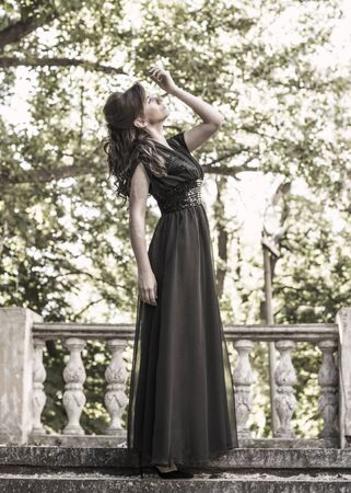 Beautiful girl in a black evening dress near the stairwell of an abandoned palace. Beautiful woman with scars. Young girl in retro style. Pretty Woman