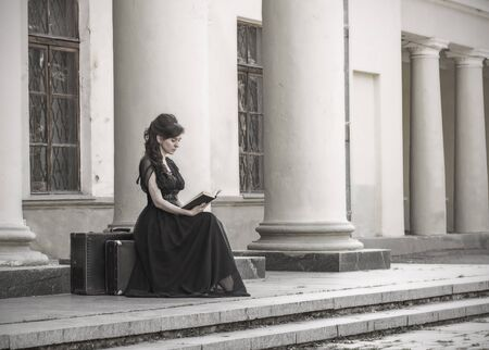 Beautiful girl in black evening sitting reading a book. A girl sits with suitcases near an old building with columns. Beautiful woman with scars. Retro style young girl. Pretty Woman