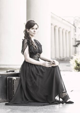 Beautiful girl in a black evening dress sits with a book. A girl sits with suitcases near an old building with columns. Beautiful woman with scars. Retro style young girl. Pretty Woman