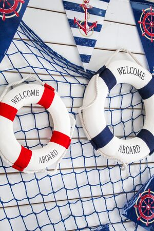 Scenery sea, marine theme. White wooden board with lifebuoys, fishing net and flags (pennants).