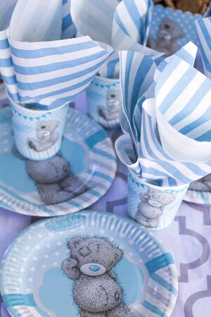 Festive table setting for children. Decoration for childrens party. Teddy bear style serving. Cups, plates and napkins are white-blue. Stock Photo