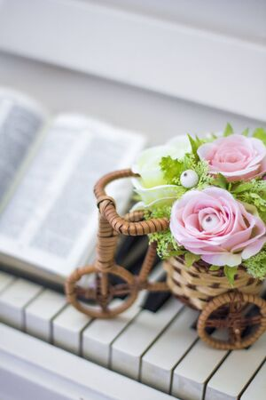 Decorative flowers (roses) in a wicker bicycle on the piano and the Bible. Topiary. Wedding decor, decoration. Close-up.