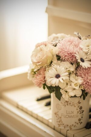 Bouquet of flowers in a beautiful box on a white piano. Bouquet of asters, hydrangeas and daisies. Bridal bouquet. Stock Photo